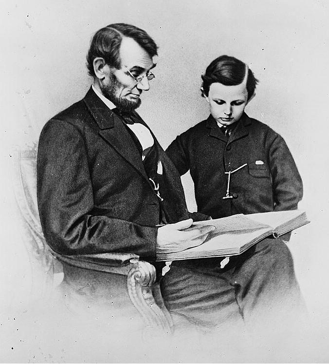 Abraham Lincoln reads with his youngest son, Tad Lincoln, in this 1864 Matthew Brady photograph.