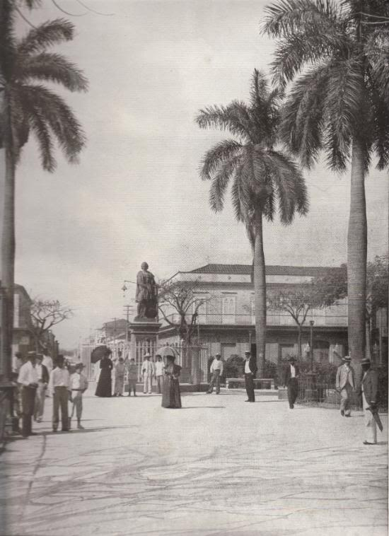PLAZA AND COLUMBUS MONUMENT, CARDENAS, CUBA: This monument was erected in 1862, by order of Isabella II of Spain, and presented to the City of Cardenas. It is one of the many costly works of art that Spain has left in the Islands as a compensation for her misrule and extortion. The stately date palms on either side form an appropriate frame for a strikingly beautiful picture.