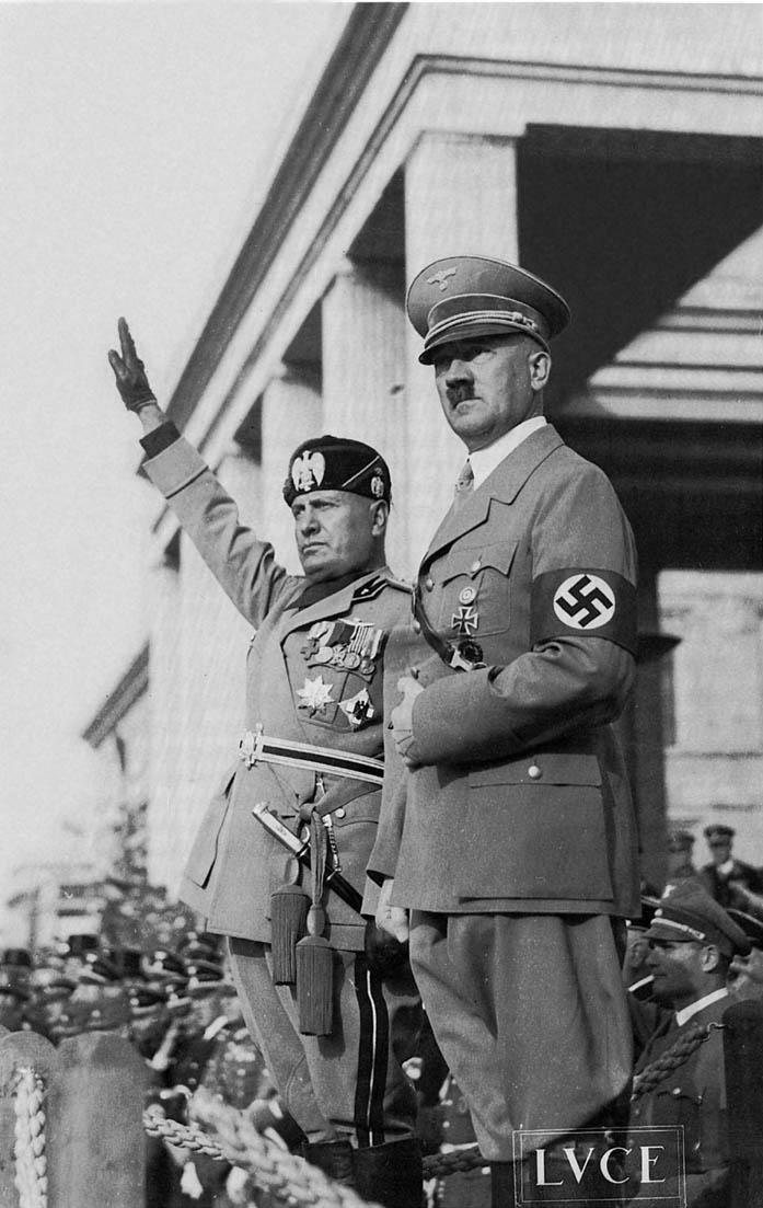 "Benito Mussolini (left) and Adolf Hitler on October 25, 1936, when an Axis was declared between Italy (led by Fascist dictator Mussolini) and Germany (led by Nazi dictator Hitler). The ""Lvce"" logo in the bottom right of the photograph indicates that this photograph was taken by the Istituto Luce, an Italian news agency that published Fascist propaganda."
