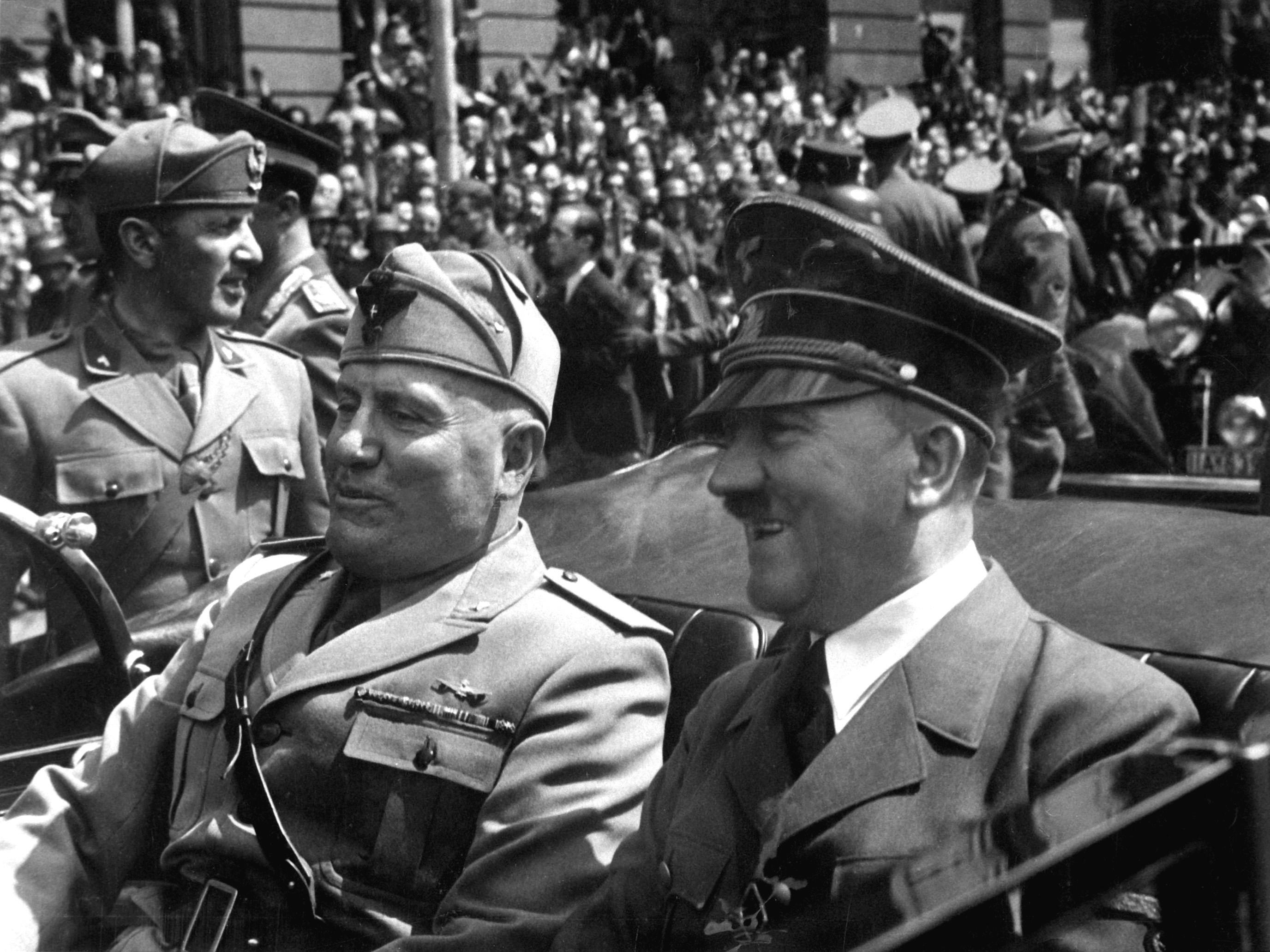 Benito Mussolini (left) and Adolf Hitler (right) riding through the streets of Munich, Germany, in 1940. Mussolini (Italy) and Hitler (Germany) formed an Axis in 1936.