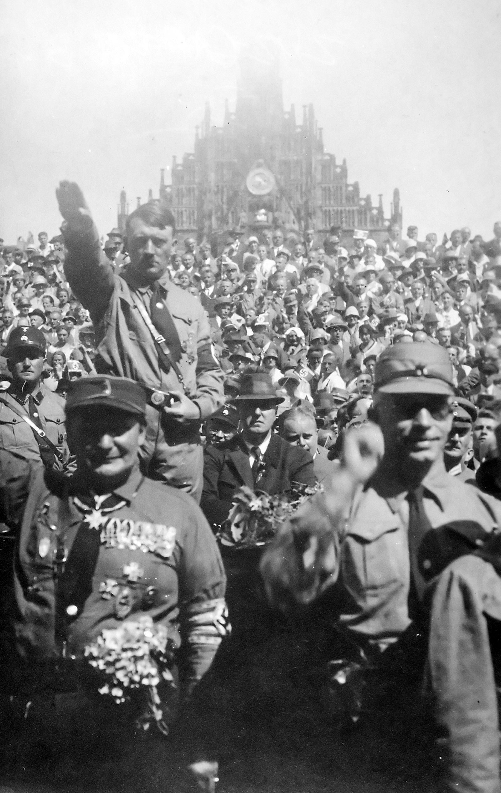 Adolf Hitler at a Nazi Party rally in Nuremberg, Germany, in 1928. Hitler is standing. In front of Hitler is Hermann Göring. Hitler, a veteran of World War I and out-of-work painter, would ultimately become dictator of Germany.