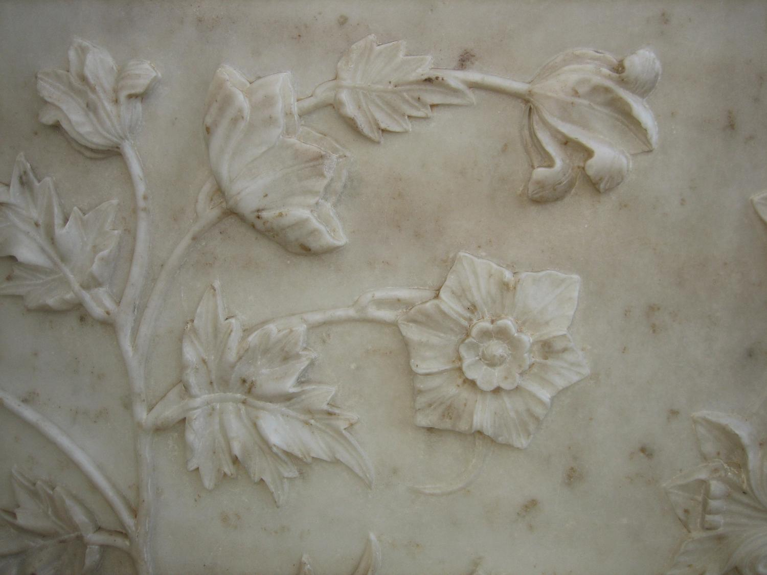 A realistic bas-relief floral design in marble at the Taj Mahal. The Taj Mahal is located in Agra, India. The Taj Mahal was built by Shah Jahan as a memorial to his favorite wife.