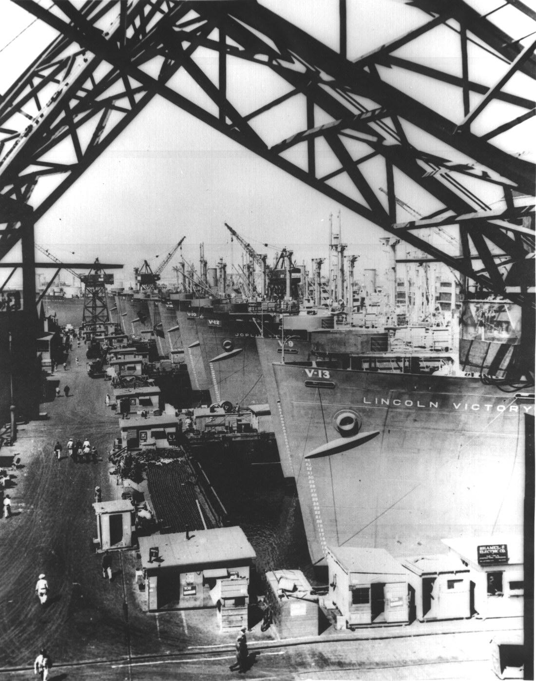 Victory cargo ships are lined up at a U.S. west coast shipyard for final outfitting before they are loaded with supplies for Navy depots and advance bases in the Pacific.